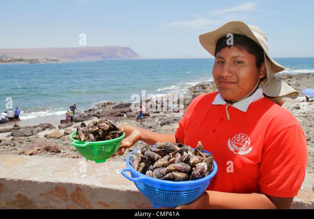 Chile Arica Pacific Ocean coast seashore artisan fishing industry harvesting marine species shellfish Hispanic boy - Stock Image