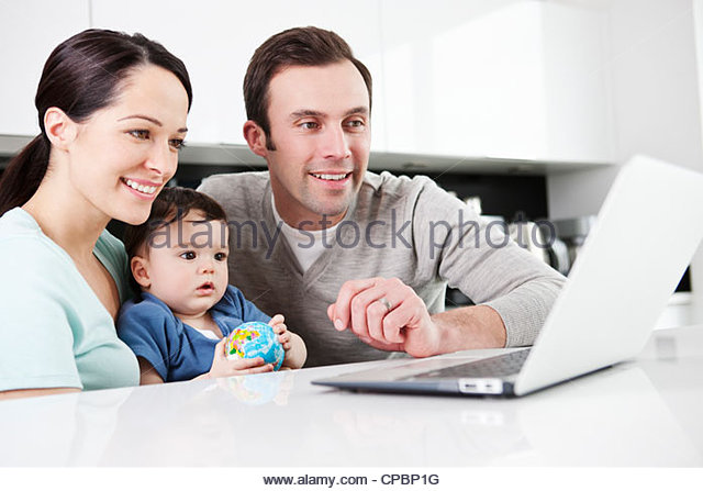 A couple and their baby son looking at a laptop, baby holding a globe ball - Stock Image