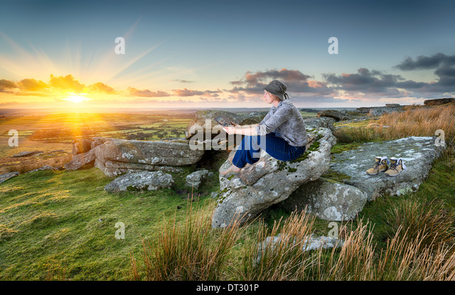 Woman out hiking, relaxing and using a tablet pc at sunset on a rocky tor on Bodmin Moor in Cornwall - Stock-Bilder