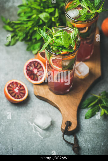 Blood orange lemonade with mint and ice in tall glasses - Stock Image