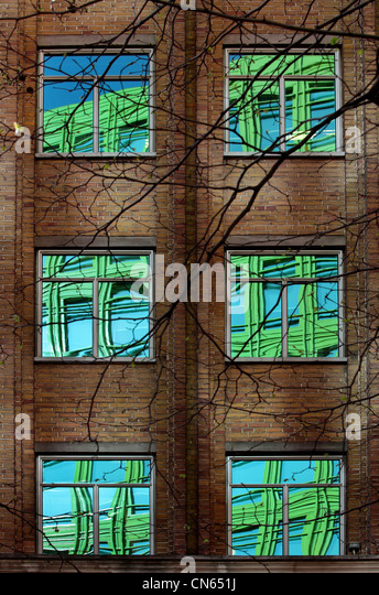 Reflections of green office block in the windows of an older building in London - Stock Image