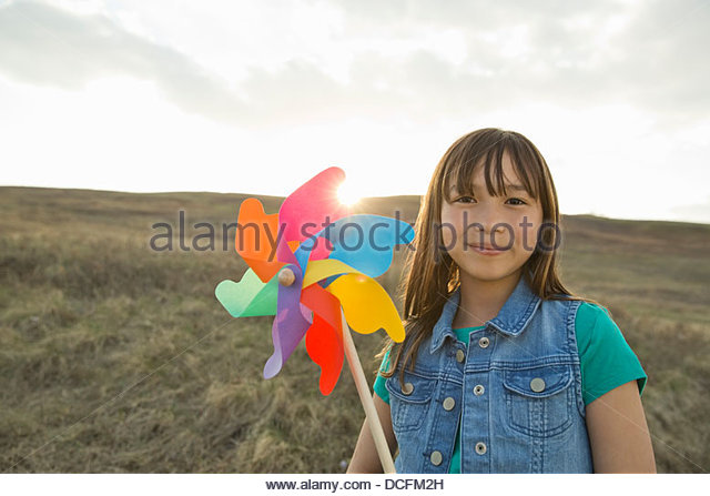 Portrait of schoolgirl holding pinwheel on hillside - Stock-Bilder