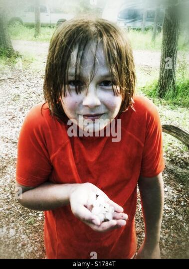 A wet boy holds hailstones from a summer storm. - Stock Image