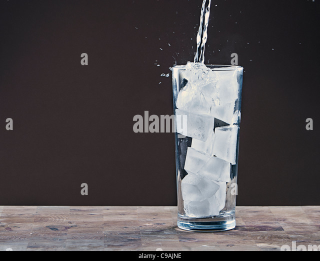 Pouring Water into Glass Full of Ice Cubes - Stock Image