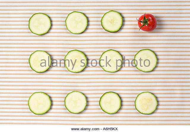 Tomato amongst courgette slices - Stock Image