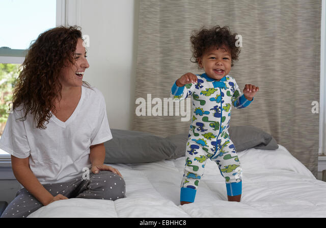 Young woman watching toddler son jumping on bed - Stock Image