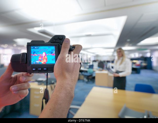 Office workers taking thermal infrared images in office to check heat efficiency - Stock Image