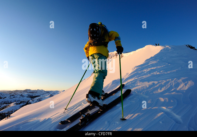 A skier skinning up a snow covered slope at sunrise in the Sierra Nevada near Lake Tahoe, California. - Stock Image