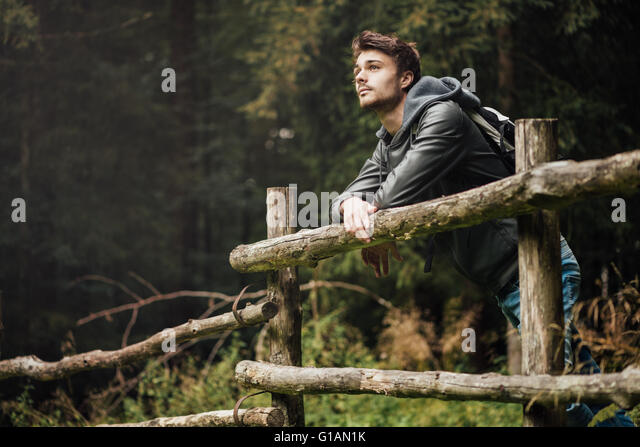 Young man with backpack hiking in the forest and leaning on a wooden fence, nature and physical exercise concept - Stock-Bilder