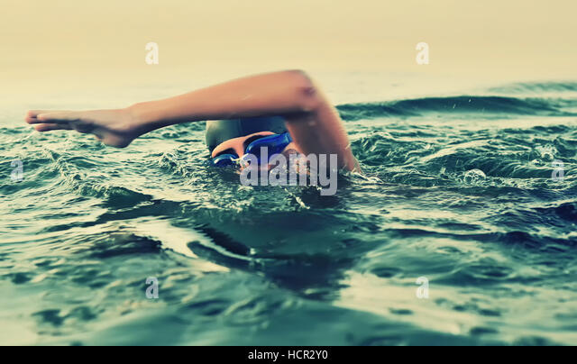 Close up of young boy swimming in sea - Stock Image