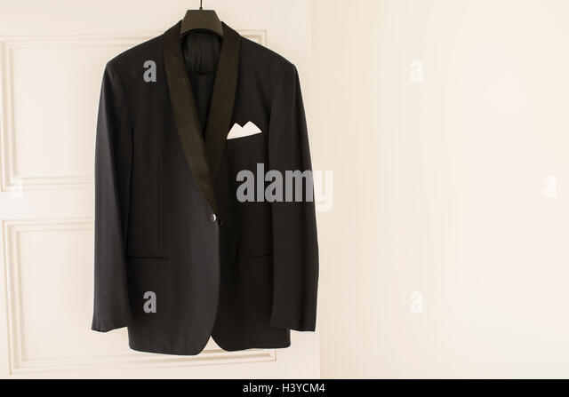 Black dinner jacket hanging from door on clothes hanger in empty white room. Wall with copy space. - Stock-Bilder