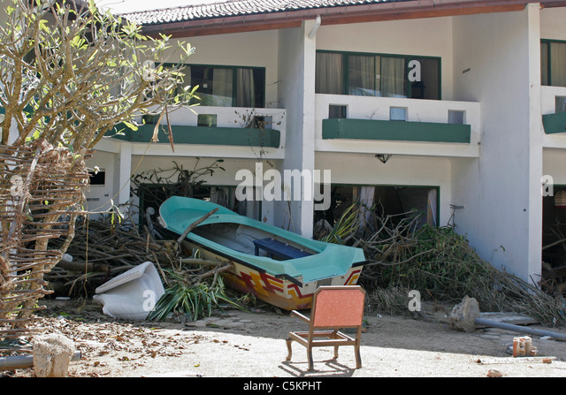Sri Lanka, motel on SW coast near Beruwela damaged by 2004 tsunami, small boat washed ashore - Stock Image