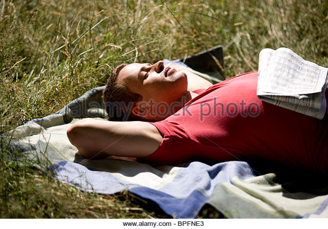 A young man lying in the sun - Stock Image