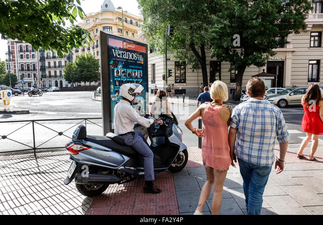 Spain Europe Spanish Hispanic Madrid Centro Chamberi Plaza Alonzo Martinez pedestrians SYM MaxSYM motor scooter - Stock Image