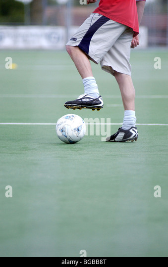 Photograph of football placing dribbling student astro turf ball - Stock-Bilder