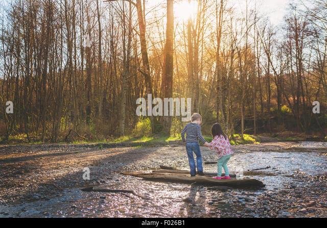 Boy helping girl walk across a log - Stock Image