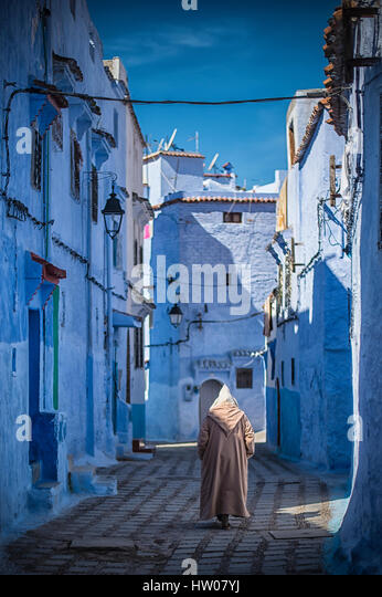 Man with a traditional dress is walking in the blue medina of Chefchaouen, Morocco. - Stock Image