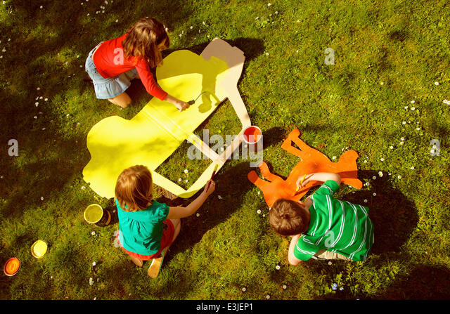 Children Painting Cardboard Cut Outs in Garden - Stock Image