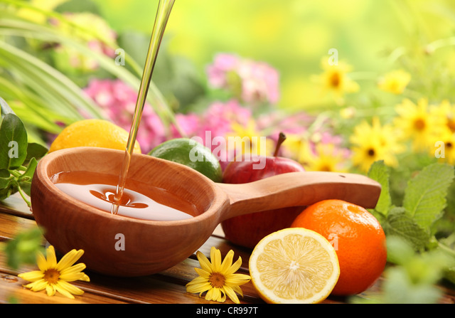 Honey and fresh fruits with flowers background,closeup. - Stock Image
