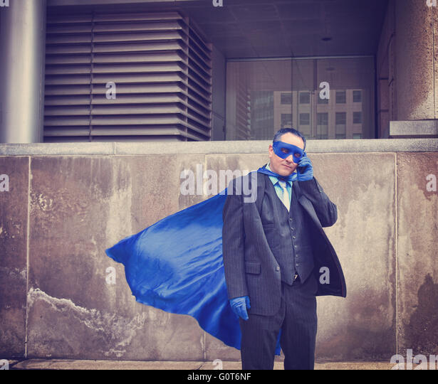 A business man is dressed up as a super hero using a phone in the city for a unique humorous or communication concept. - Stock Image