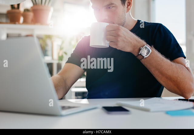 Image of young businessman with cup of coffee looking at laptop screen at workplace. Male executive working at his - Stock Image