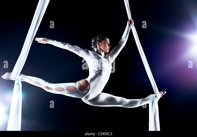 Young woman gymnast. On black background with flash effect. - Stock-Bilder