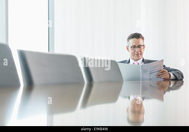 Middle-aged businessman reading book at conference table - Stock Image