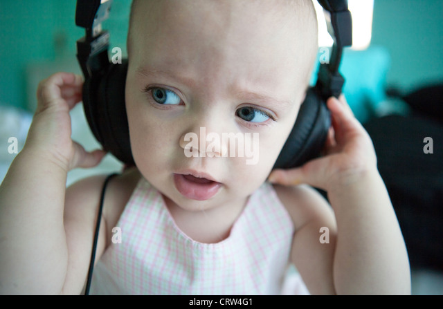One year old listening intently to sound on headphones, closeup. - Stock-Bilder