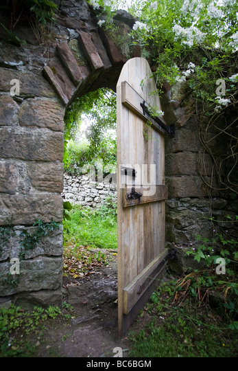 Traditional oak half open doorway in garden wall with stone surrounds and arch,overhung with plants and ivy - Stock-Bilder