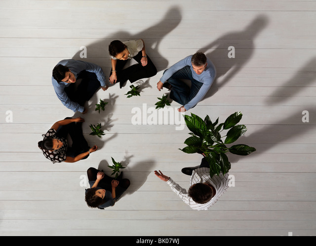 group of people on floor with plants - Stock Image