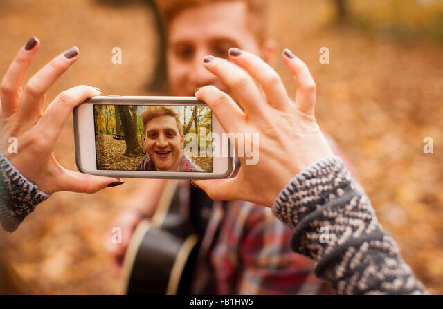 Hands of young woman photographing boyfriend on smartphone in autumn forest - Stock-Bilder