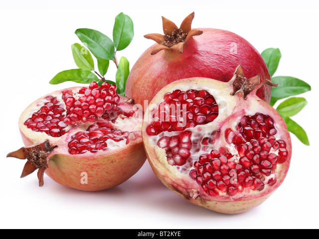 Juicy opened pomegranate with leaves. Isolated on a white background. - Stock Image