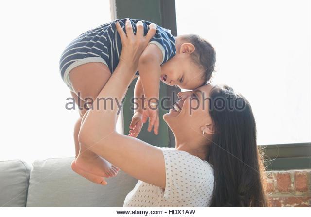 Smiling Hispanic mother lifting baby son - Stock Image