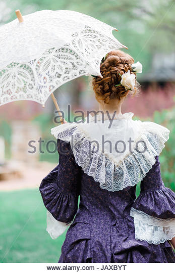 Rear view of a Victorian woman holding a parasol - Stock Image