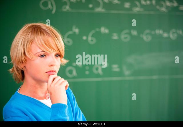 Schoolboy at blackboard thinking about formula - Stock Image