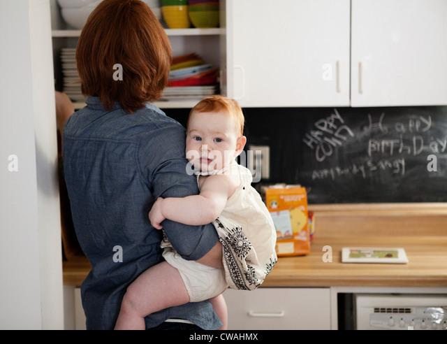 Mother holding baby daughter in kitchen - Stock-Bilder