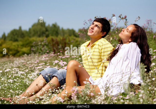 Portrait of attractive man and woman relaxing on the glade - Stock Image