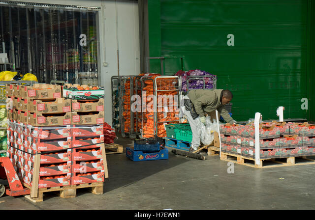 Worker packing vegetables at the New Covent Garden vegetable and fruit market. Vauxhall, London, UK - Stock Image