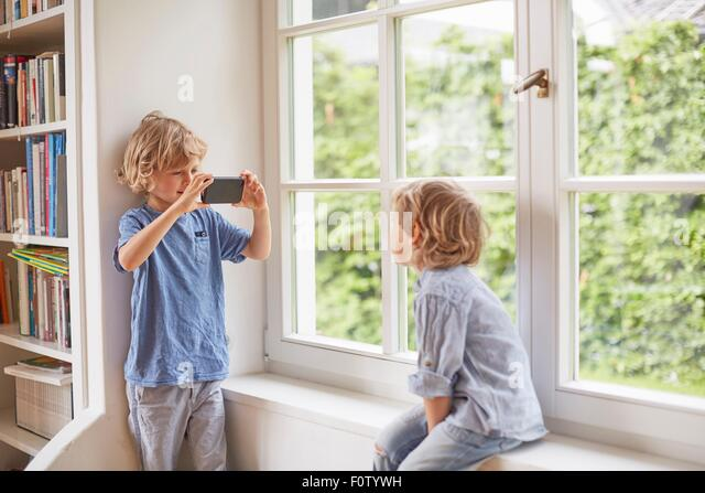 Young boy taking photograph of brother, using smartphone - Stock Image