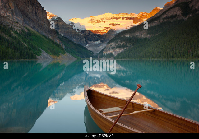 Canoe on Lake Louise at sunrise, Banff National Park, UNESCO World Heritage Site, Alberta, Rocky Mountains, Canada - Stock Image