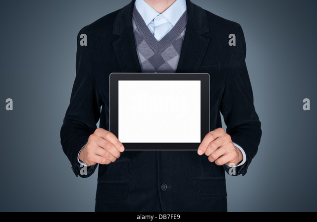 Handsome businessman in black suit showing modern digital tablet with blank screen. Studio shot. Isolated on dark - Stock Image