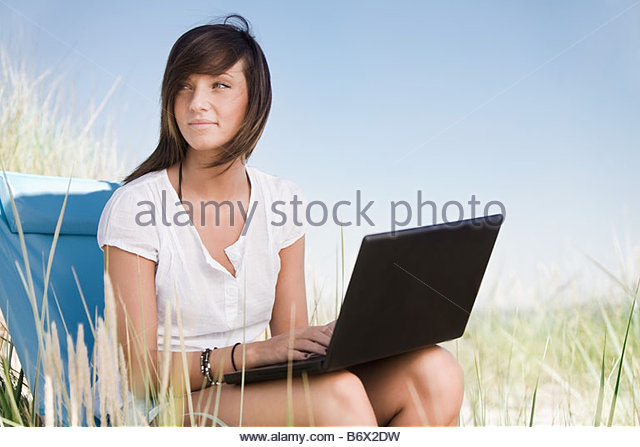 Girl with computer on beach - Stock Image
