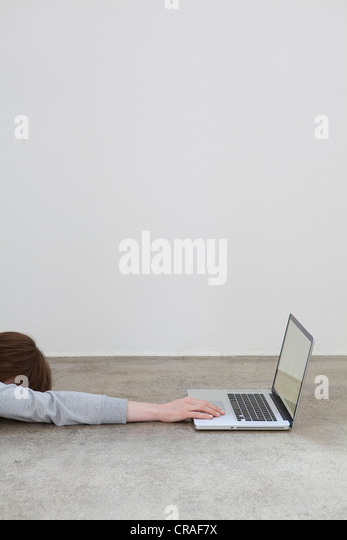 Woman has reached out for a laptop and fallen asleep - Stock Image