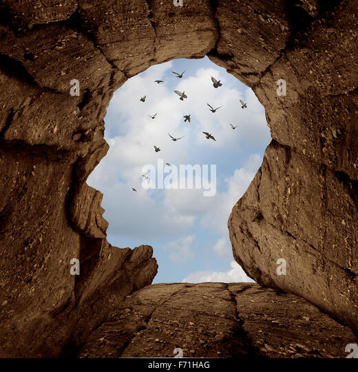 Imagination and discovery concept as a rocky cliff with an opening on top shaped as a human head as a new life metaphor - Stock Image
