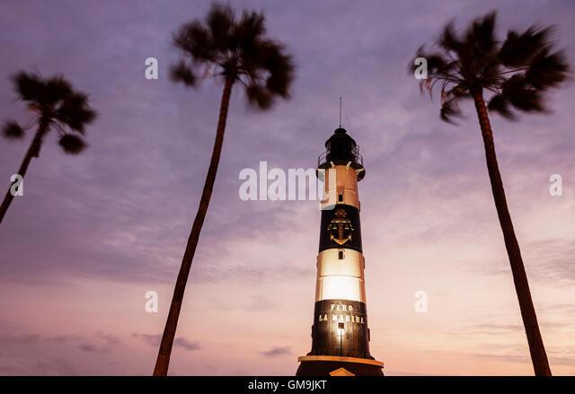 Peru, Lima, Miraflores, Faro De La Marina and palm trees at sunset - Stock Image