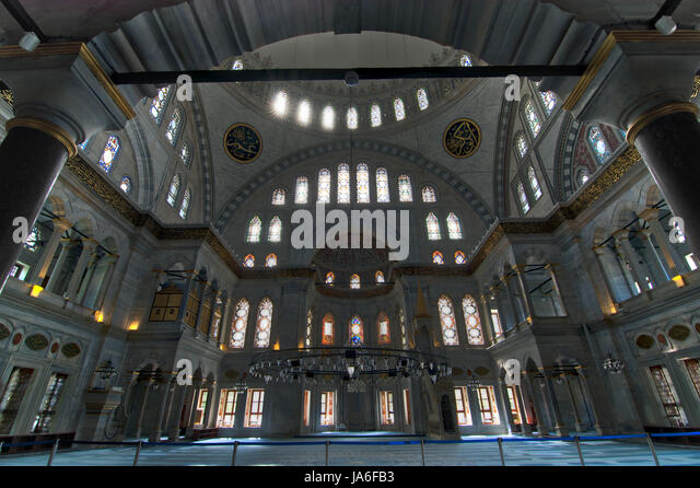Interior of Nuruosmaniye Mosque, Istanbul, Turkey, with huge arches, decorated domes and colored stained glass windows - Stock Image