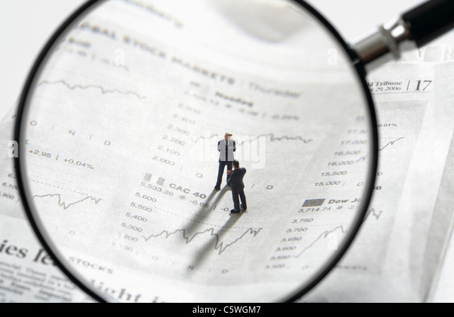 Two figurines on newspaper stock quotes with magnifying lens in foreground - Stock Image