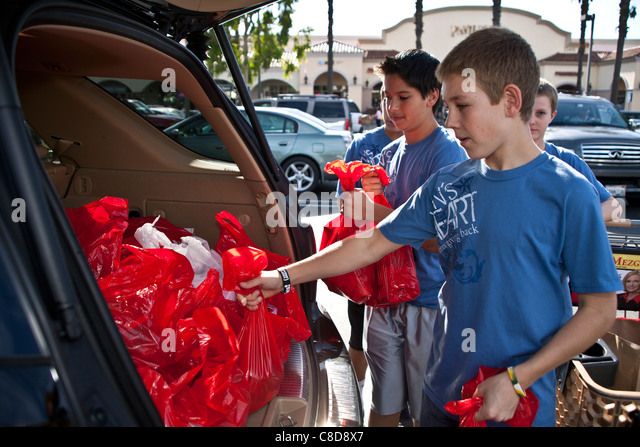 Two 2 teen boys multi ethnic from Lion's Heart organization collecting donations for food bank. Editorial only - Stock Image