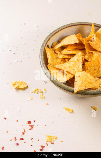 Bowl of corn nachos chips over white wooden background. - Stock Image