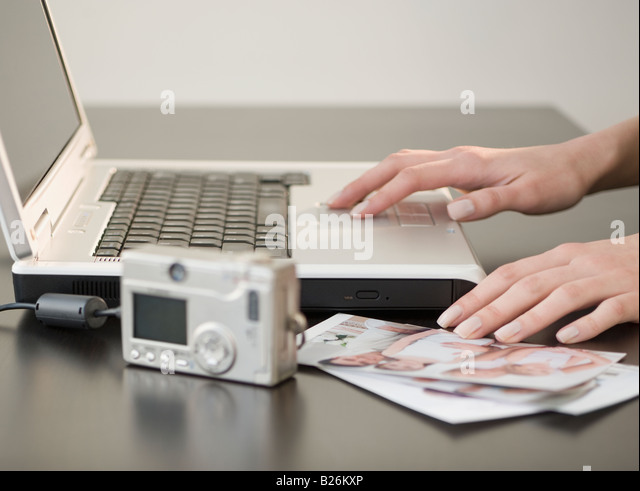 Digital camera and photographs next to laptop - Stock Image